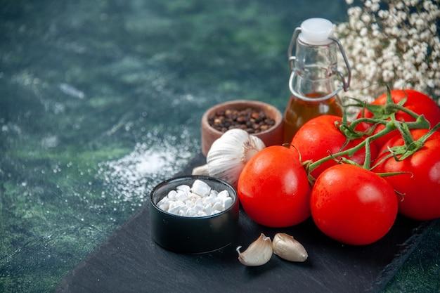 Vista frontale ravvicinata pomodori rossi freschi con condimenti sulla superficie scura colore pasto cibo foto salute dieta insalata