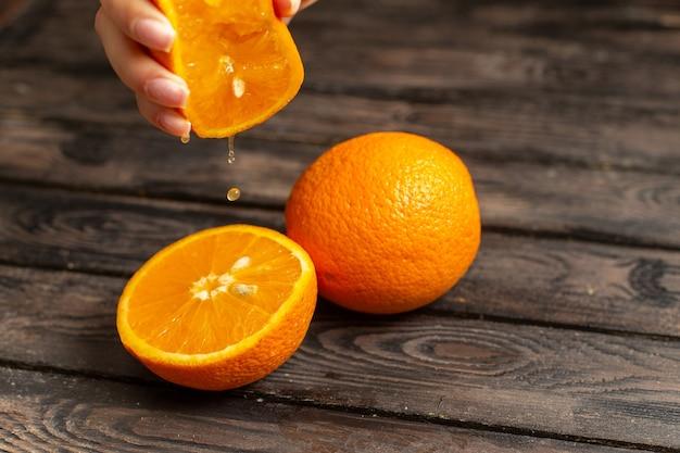 Vista ravvicinata anteriore arance fresche acide succose e pastose isolate su fondo rustico marrone frutta agrumi tropico succo fresco