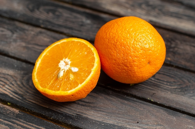 Vista ravvicinata anteriore arance fresche acide succose e pastose isolate su fondo rustico marrone frutta agrumi tropico fresco succo acido