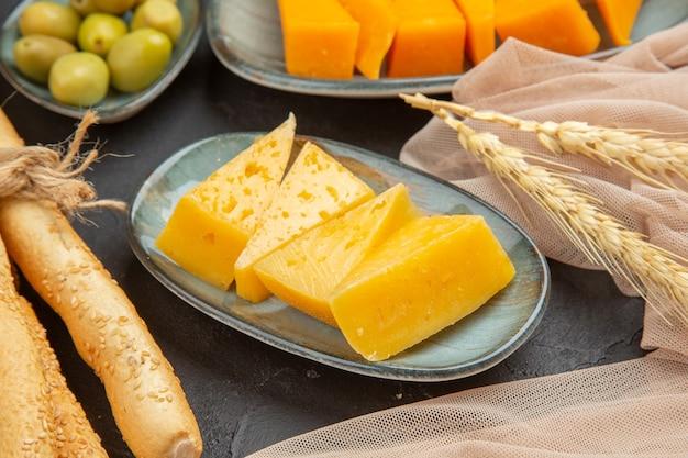 Vista frontale ravvicinata di fette di formaggio fresco e gustoso su un asciugamano e olive verdi su sfondo nero