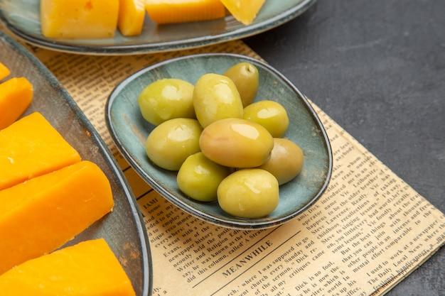 Vista frontale ravvicinata di vari formaggi freschi a fette e olive verdi su un vecchio giornale su sfondo nero