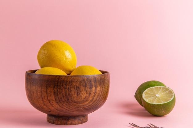 ピンクの壁の茶色の鍋の中の正面のクローズビュー新鮮な黄色のレモン