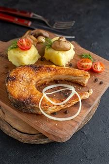 Vista frontale ravvicinata della farina di pesce fritta con funghi, verdure, formaggio e posate su tavola di legno su superficie nera angosciata