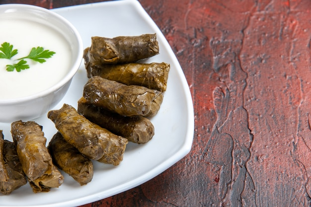 Front close view of green leaf dolma with yogurt on dark surface