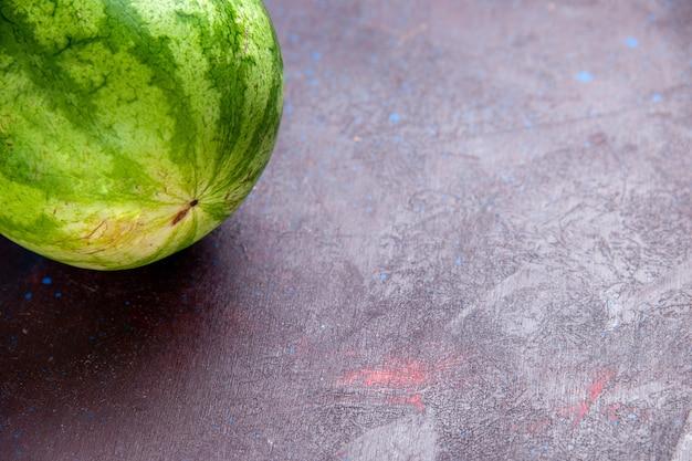 Frutta fresca dell'anguria verde di vista ravvicinata anteriore sul succo di estate della bacca della frutta del fondo scuro