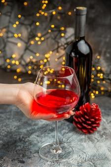Vista frontale ravvicinata della mano che tiene un bicchiere di vino rosso secco e bottiglia su sfondo grigio