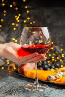 Vista frontale ravvicinata della mano che tiene un bicchiere di vino rosso secco e uno spuntino delizioso su sfondo grigio