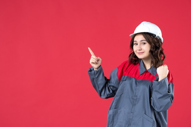 Front close view of happy smiling female builder in uniform with hard hat and pointing up on isolated red wall