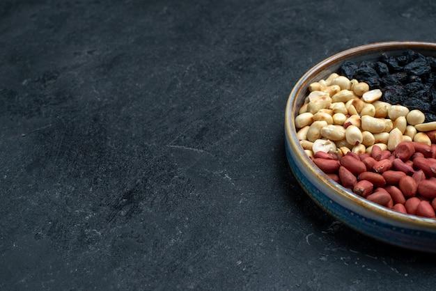 濃い灰色の表面にある正面のヘーゼルナッツとレーズンおよびその他のナッツ