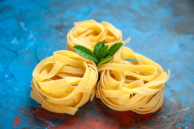 Front close view of homemade fresh tagliatelle pastas with green on blue background