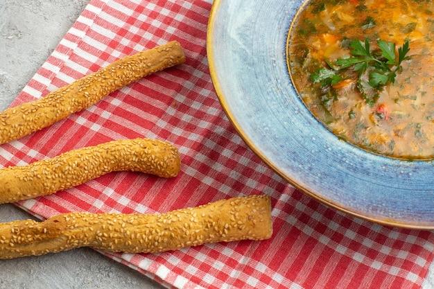 Zuppa di verdure calda vista frontale ravvicinata con verdure all'interno del piatto su uno spazio bianco