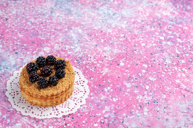 Вид спереди крупным планом маленький торт ежевики на светло-розовом фоне.
