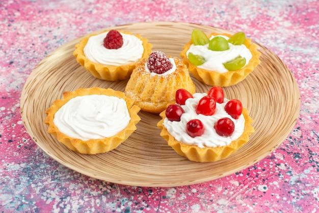 フロント近くの明るい表面のクッキーに新鮮なクリームとフルーツの小さなケーキを表示します。