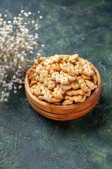 Vista frontale ravvicinata piccoli cracker all'interno del piatto su sfondo scuro spuntino croccante sale pane fette biscottate colore