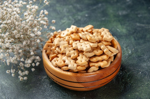 Vista frontale ravvicinata piccoli cracker all'interno del piatto su sfondo scuro spuntino croccante sale pane fette biscottate colorante alimentare