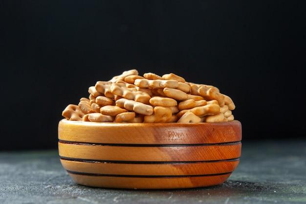 Вид спереди крупным планом маленькие крекеры внутри тарелки на темном фоне хрустящие закуски, соленые сухарики, пищевые чипсы, цвет