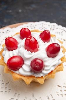 正面を閉じる暗い表面のクリームフルーツと赤いフルーツの小さなおいしいケーキケーキフルーツビスケット甘い