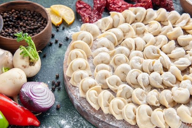 Vista frontale ravvicinata piccoli gnocchi crudi con farina e verdure su pasta di carne scura piatto alimentare pasto calorico colore cuocere verdura