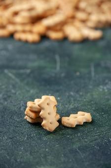 Vista frontale ravvicinata piccoli cracker di sale su sfondo scuro sale pepe colore snack cips pane