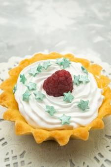 Вид спереди крупным планом маленький вкусный торт со сливочными звездными конфетами и малиной на сладком тесте на светлом столе