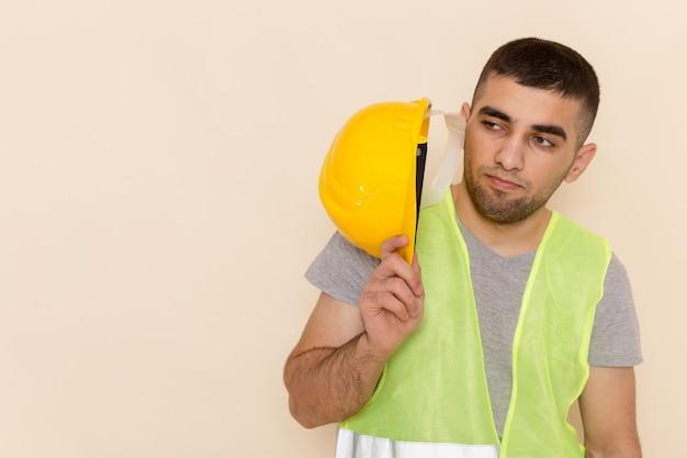 明るい背景に黄色の保護用のヘルメットを保持しているフロントビューを閉じる男性ビルダー