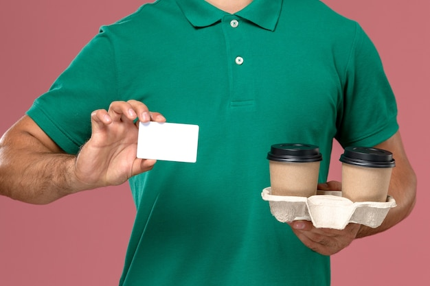 Corriere maschio di vista ravvicinata anteriore in uniforme verde che tiene tazze di caffè marrone di consegna e carta di plastica bianca sul fondo rosa dello scrittorio