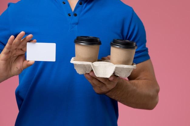 Вид спереди крупным планом мужской курьер в синей форме с доставкой кофейных чашек и белой карточкой на розовом, единообразная доставка услуг