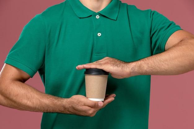 Вид спереди крупным планом мужской курьер в зеленой форме, держащий чашку кофе на светло-розовом фоне