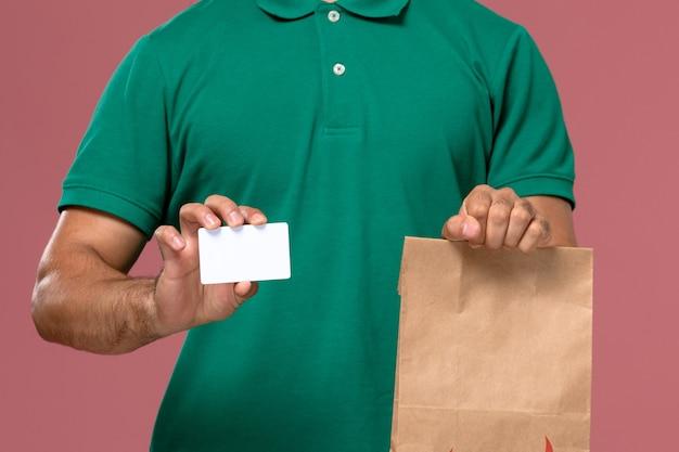 Спереди крупным планом мужской курьер в зеленой форме держит пакет с едой и карточку на розовом фоне