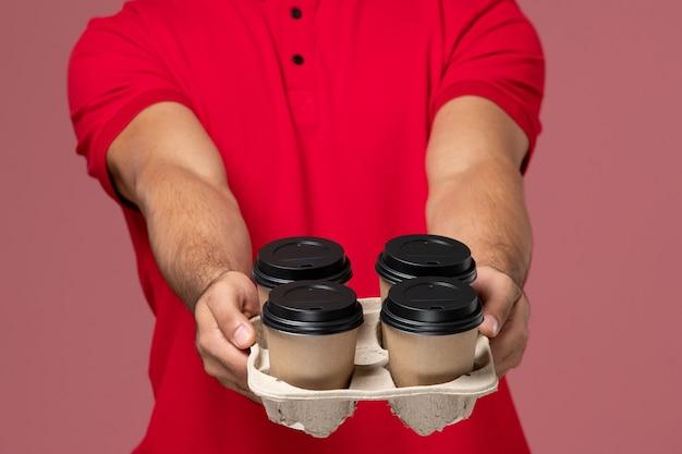 Спереди крупным планом мужской курьер в красной форме держит коричневые кофейные чашки на розовой стене