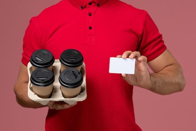 ピンクの壁に白いカードで配達コーヒーカップを保持している赤い制服の正面の拡大図男性宅配便サービス配達労働者の制服