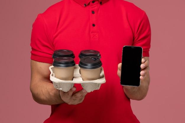 Вид спереди крупным планом мужской курьер в красной форме улыбается и держит доставку кофейных чашек с телефоном на розовой стене