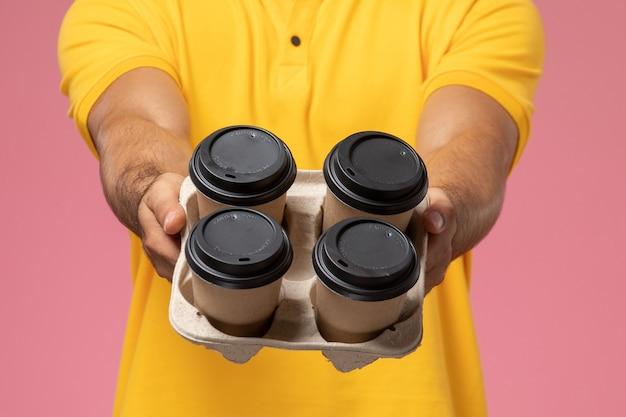 ピンクの机の上の配達のコーヒーカップを提供する黄色の制服を着た正面の男性の宅配便を閉じる