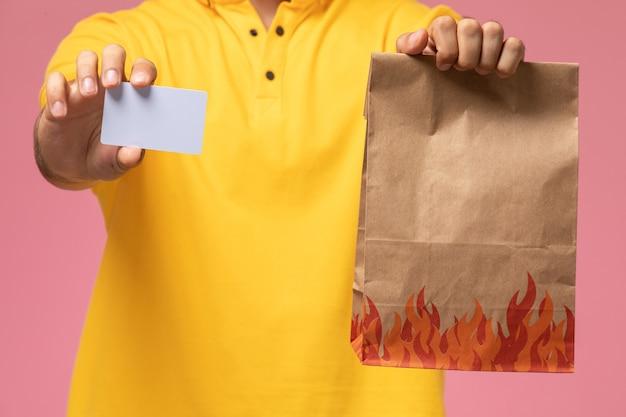 Спереди крупным планом мужской курьер в желтой форме держит серую карточку и пакет с едой на розовом столе