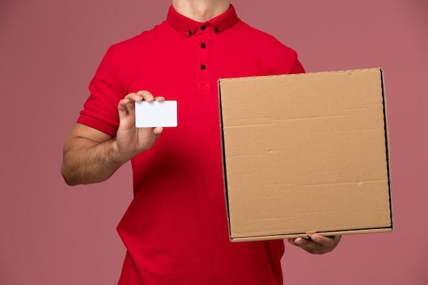 Corriere maschio di vista ravvicinata anteriore in uniforme rossa e mantello che tiene carta bianca e scatola di cibo sull'uniforme maschio di consegna di lavoro di servizio della parete rosa