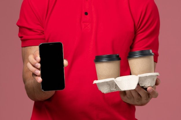 Front close view male courier in red uniform holding brown delivery coffee cups and phone on the light-pink wall