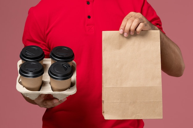 Front close view male courier in red uniform holding brown delivery coffee cups with food package on the pink wall service delivery job worker uniform