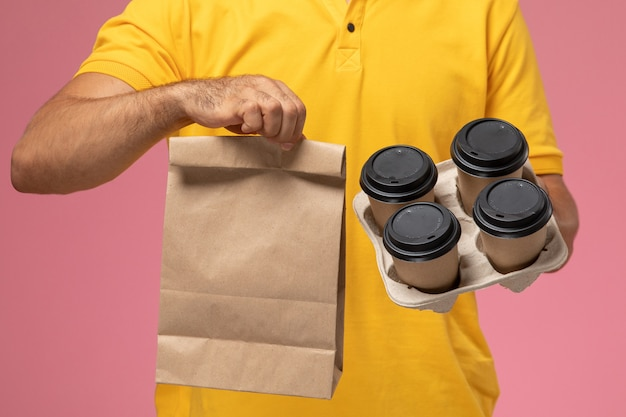 Front close view male courier in yellow uniform holding food package and delivery coffee cups on pink background