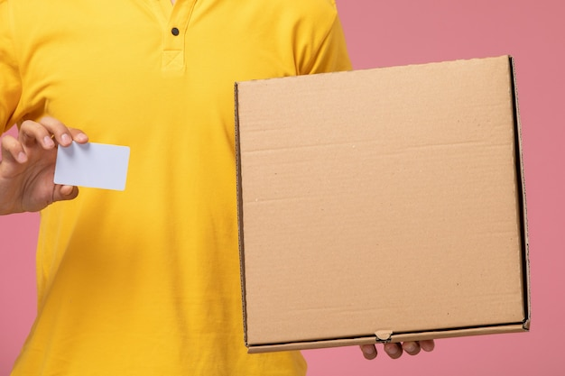 Front close view male courier in yellow uniform holding grey card and food delivery box on the pink desk