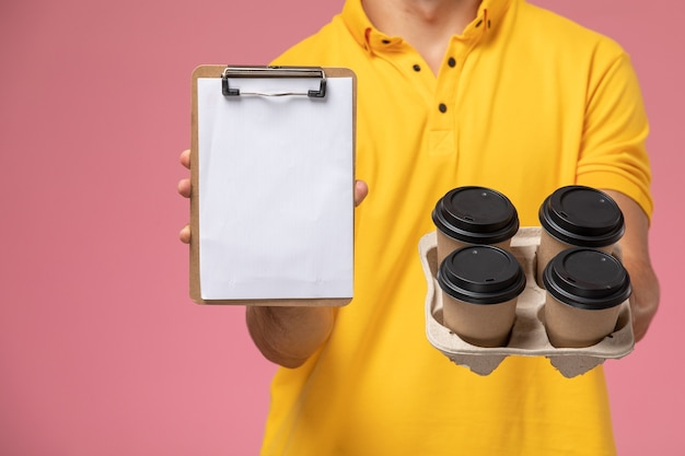 Front close view male courier in yellow uniform holding notepad and delivery coffee cups on the pink desk