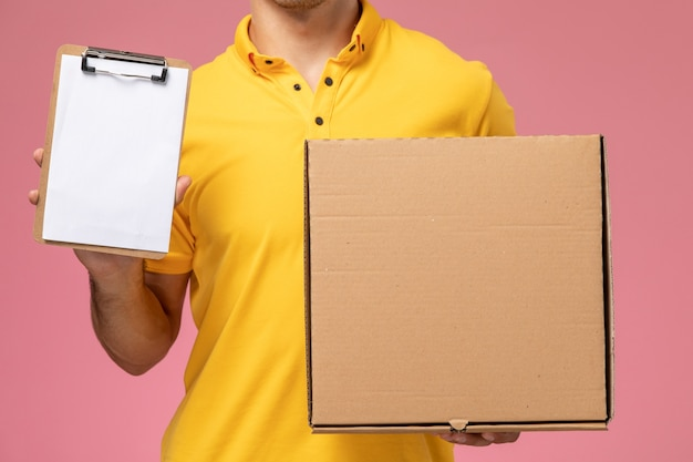 Front close view male courier in yellow uniform holding notepad and food delivery box on pink background