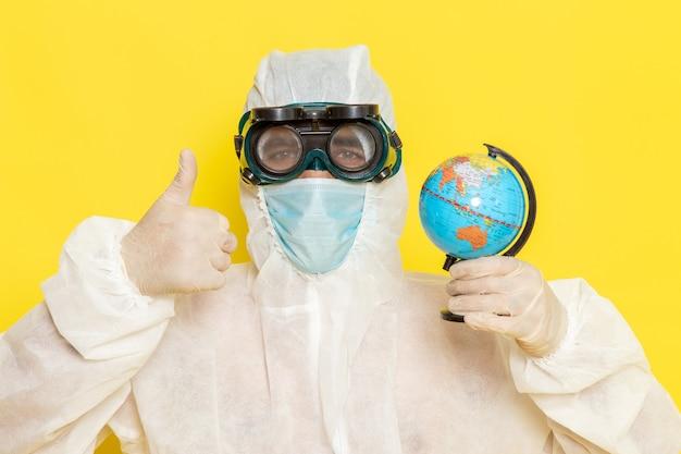 Вид спереди крупным планом мужской научный работник в специальном костюме держит маленький круглый глобус на желтом столе