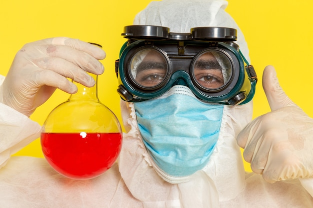 Front close view male scientific worker in special protective suit and mask holding flask with red solution on yellow desk