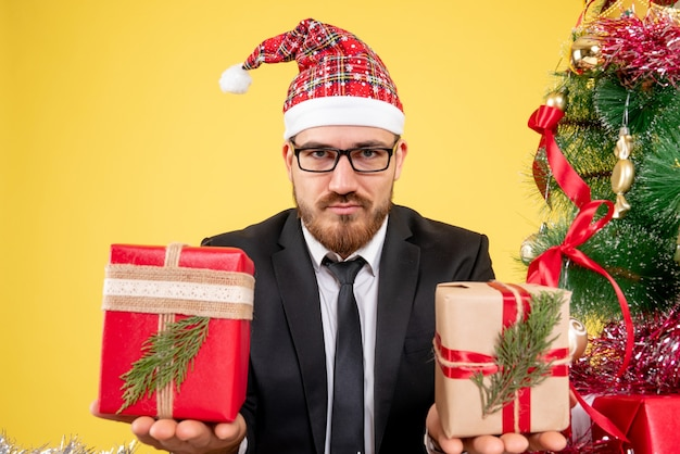 Вид спереди крупным планом рабочий-мужчина сидит вокруг рождественских подарков на желтом
