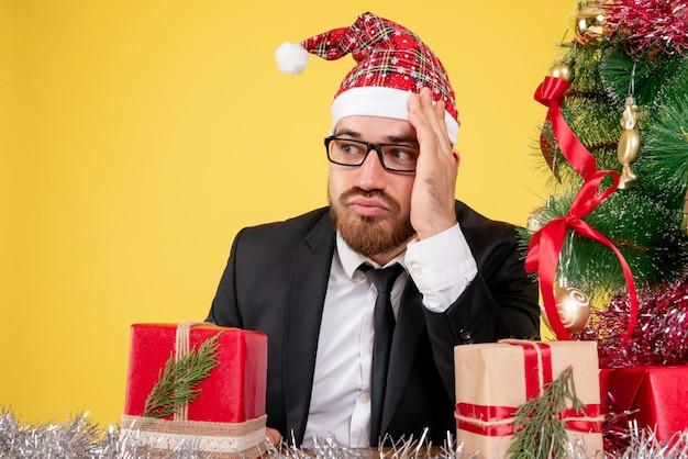 Вид спереди крупным планом рабочий-мужчина сидит вокруг подарков и деревце на желтом