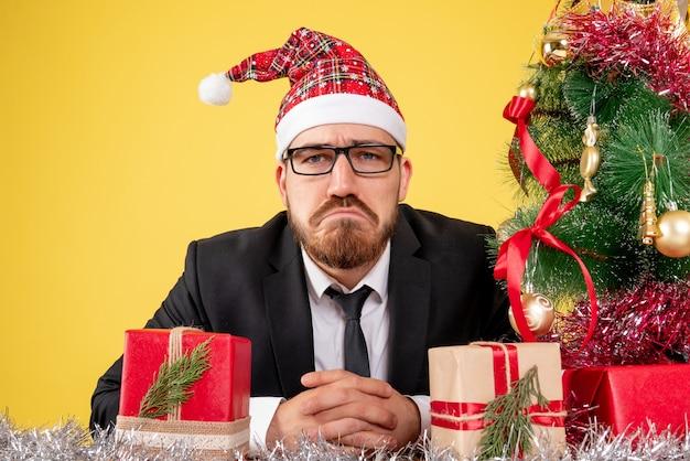 Lavoratore di sesso maschile di vista ravvicinata anteriore seduto intorno a regali e piccolo albero con la faccia triste su giallo