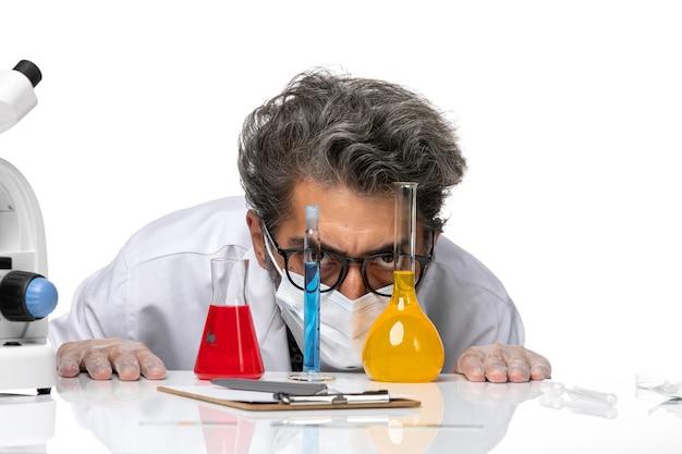 Вид спереди крупным планом ученый средних лет в специальном костюме, сидящий с растворами и смотрящий на них на белом фоне, мужская вирусология, ковид-химия