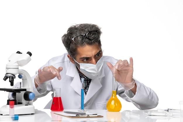 正面を見る特別なスーツを着た中年の科学者が白い背景にソリューションを持って座っている男性のウイルス科学共同化学実験室