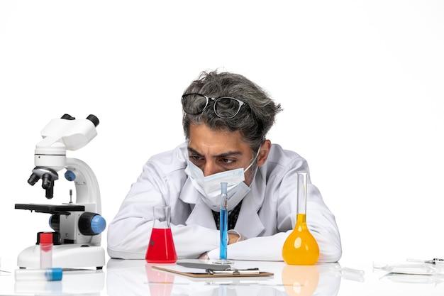 正面のクローズビュー中年の科学者は、白い背景の男性ウイルス科学covid化学のソリューションと一緒に座っている特別なスーツを着ています