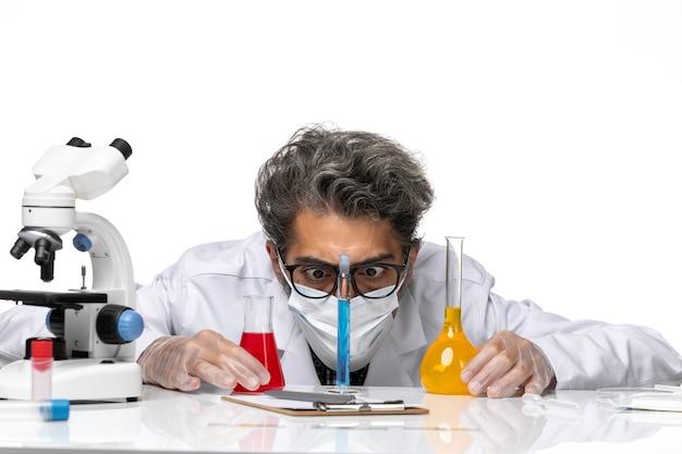 Scienziato di mezza età vista frontale ravvicinata in abito speciale seduto con soluzioni e guardandoli su sfondo bianco chimica covid scienza virus maschile